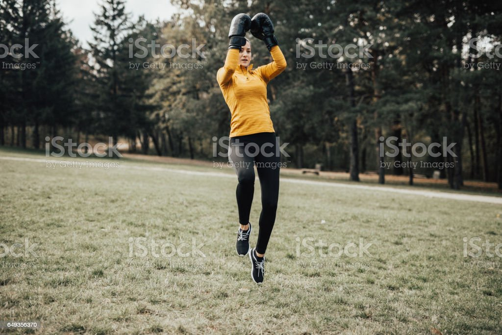 Fitness woman with boxing gloves training outdoors stock photo