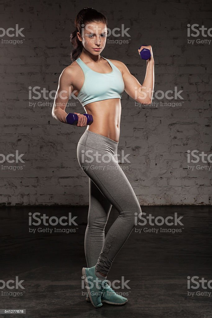 Fitness woman with muscular body, do her workout with dumbbells stock photo