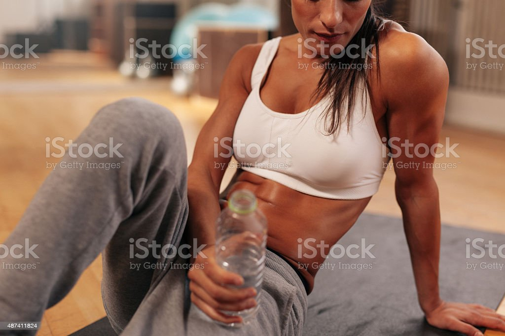 Fitness woman with water bottle at gym stock photo