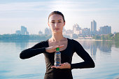 Fitness woman with water bottle at river and city backround