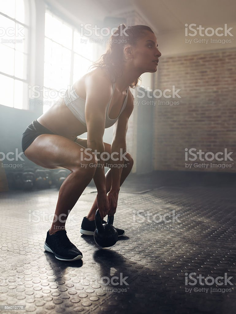 Fitness woman working out with kettle bell stock photo