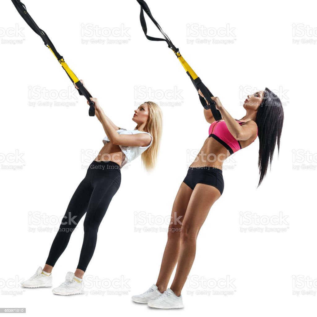 Fitness women do thrust with trx suspension stock photo