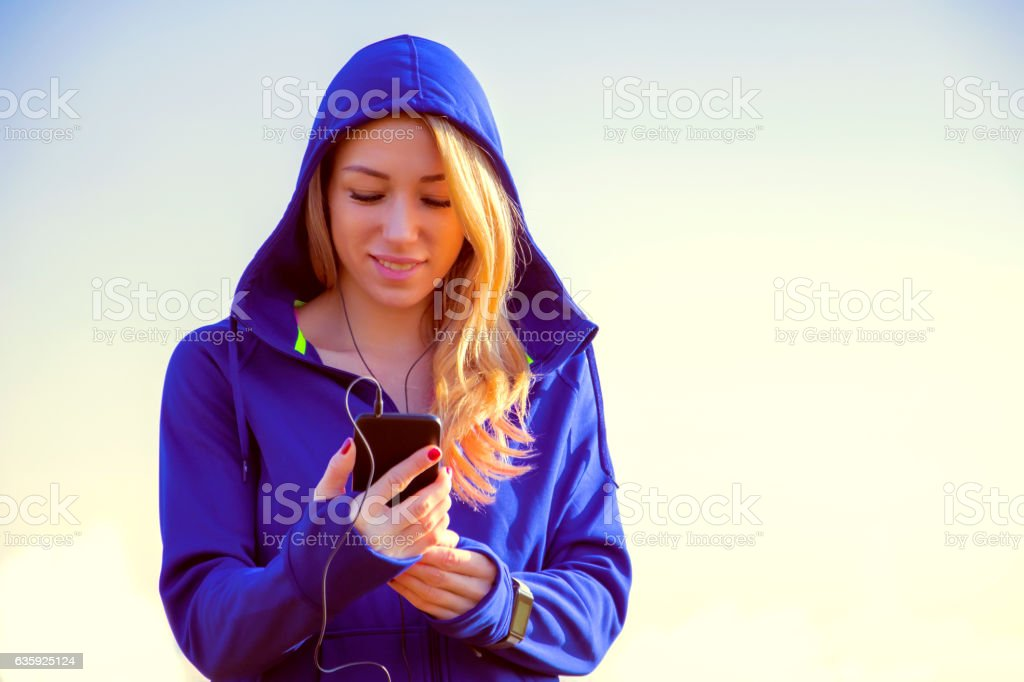 Fitness women With Smartphone In Hand Listening To Music stock photo