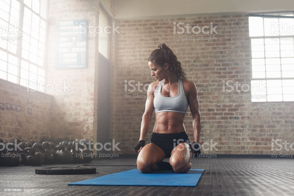 Fitness young woman sitting on yoga mat at gym stock photo