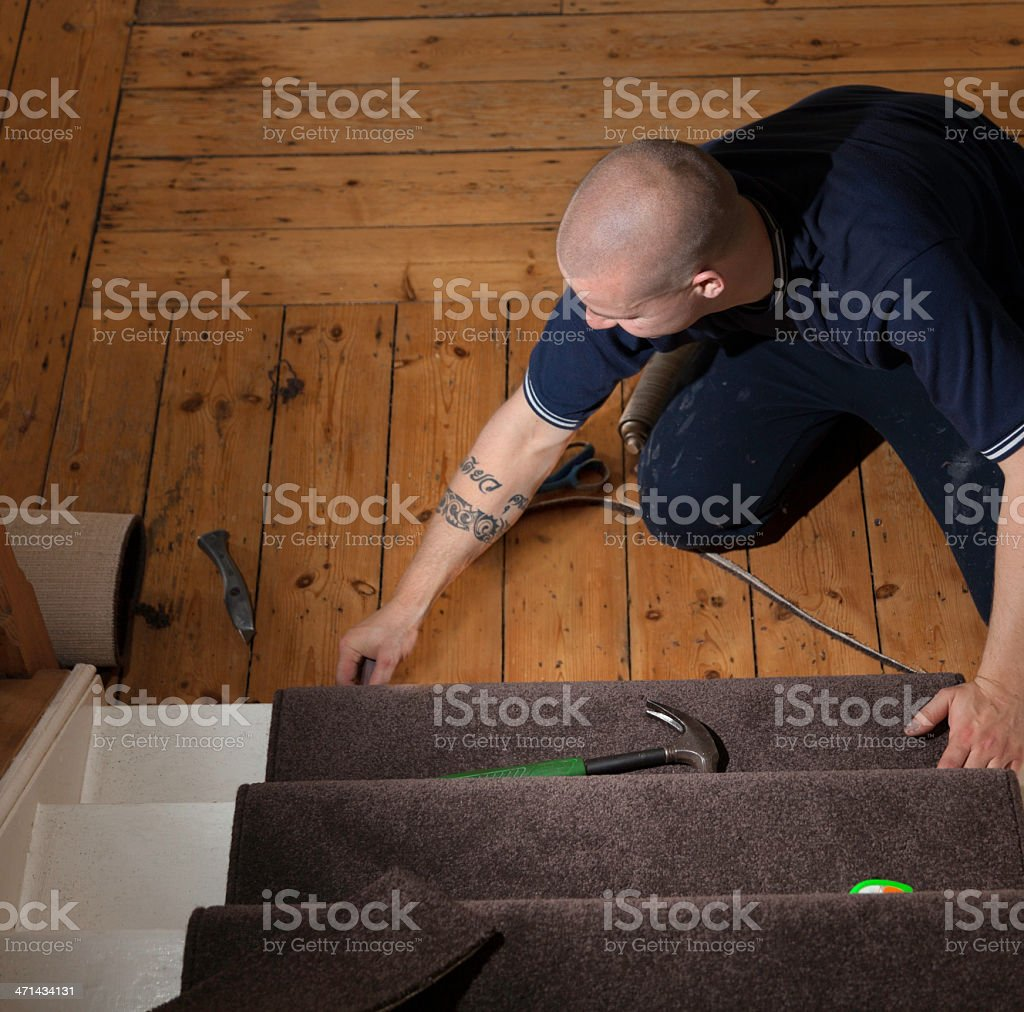 Fitter trimming stair carpet stock photo