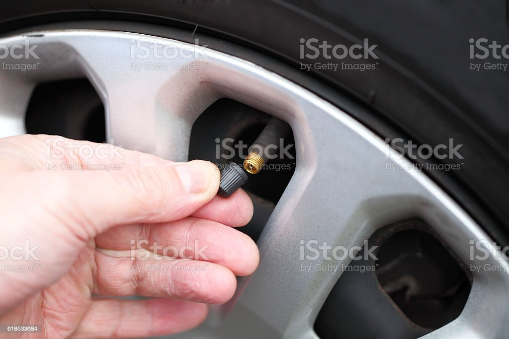 fitting cap to air valve on car tyre stock photo