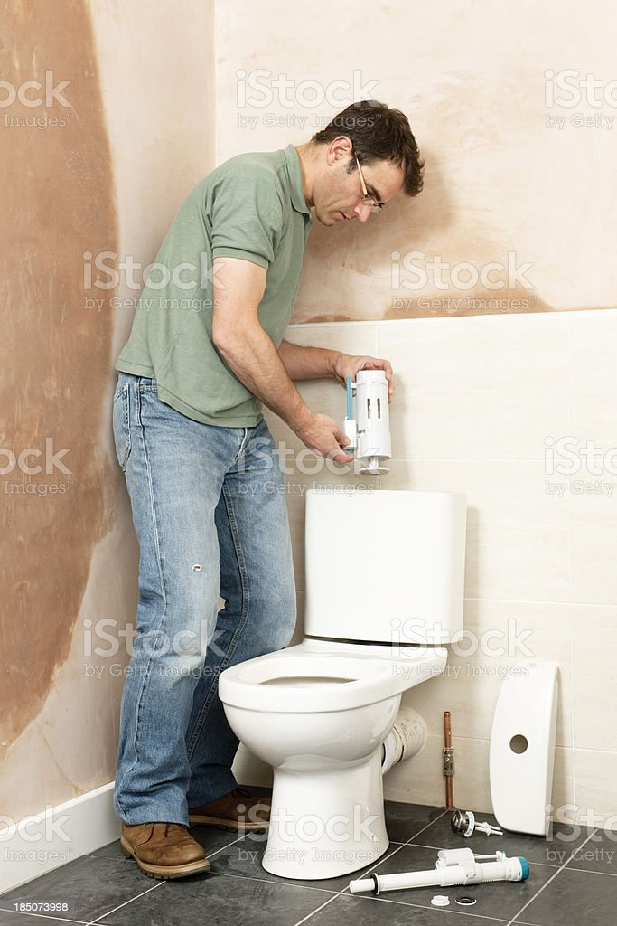 Fitting flush syphon assembly to a domestic toilet installation royalty-free stock photo