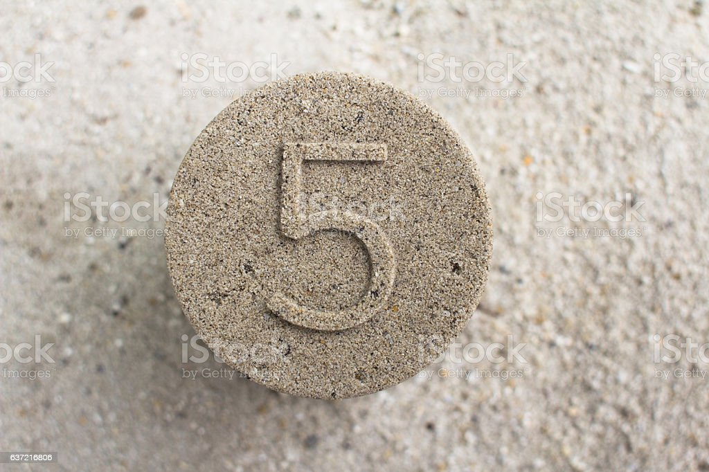 Five 5 on Sand Texture Background stock photo