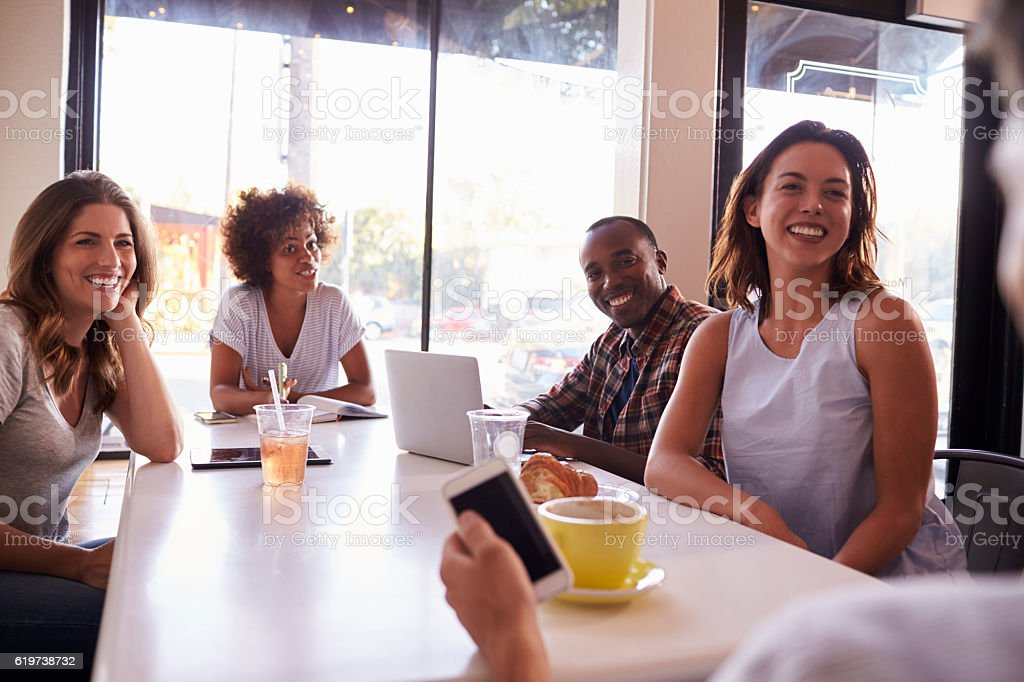 Five adult friends sitting in a cafe, over shoulder view stock photo