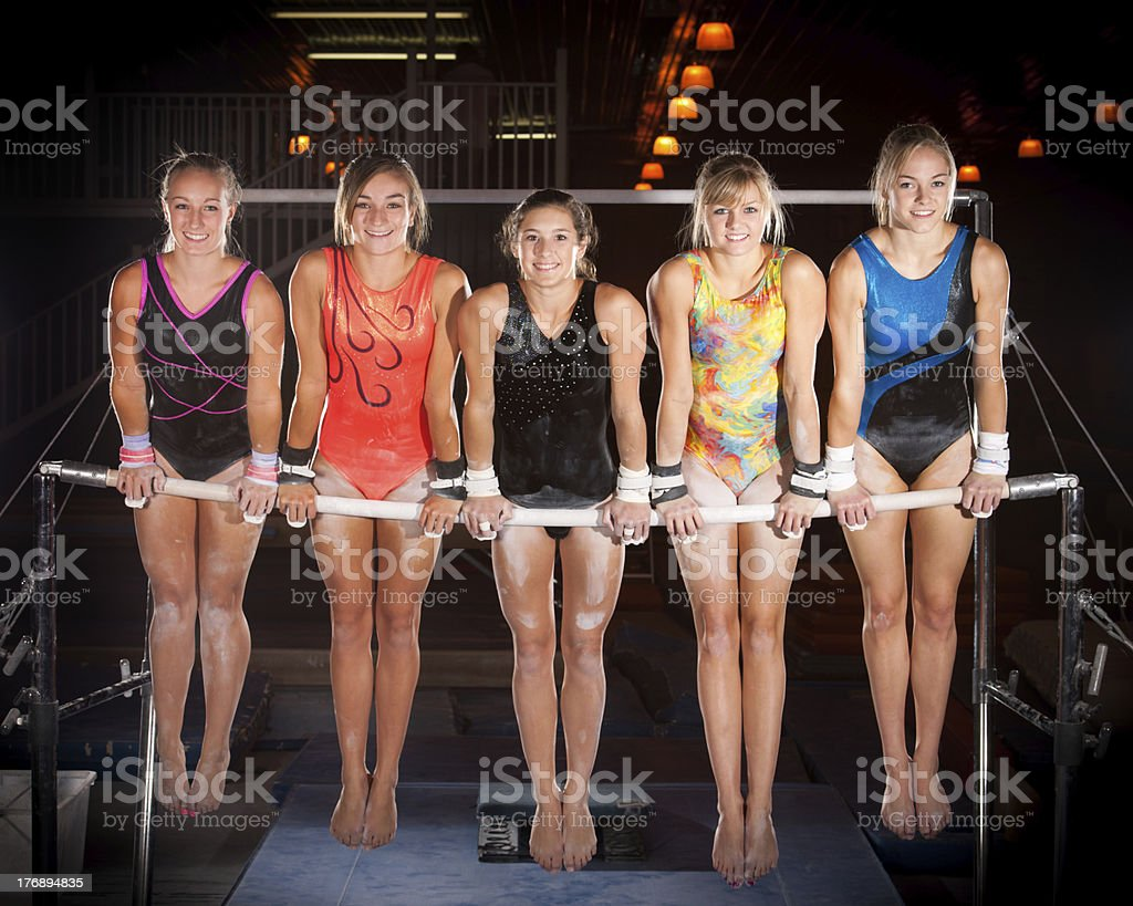 Five Advanced Gymnasts Pose on Uneven Bars royalty-free stock photo