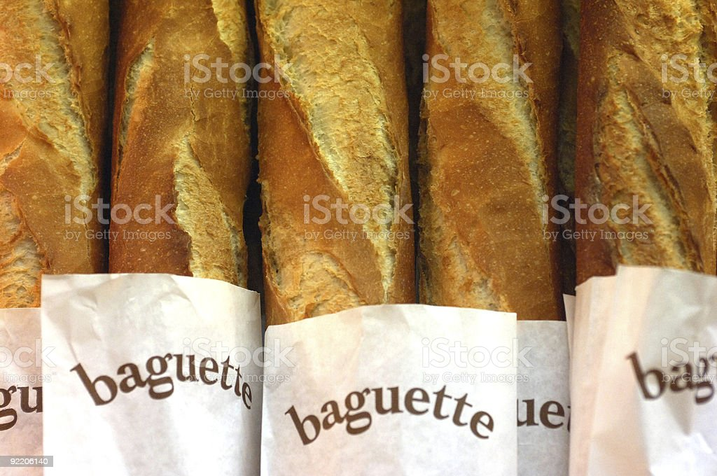 Five baguettes in white bread bags stock photo