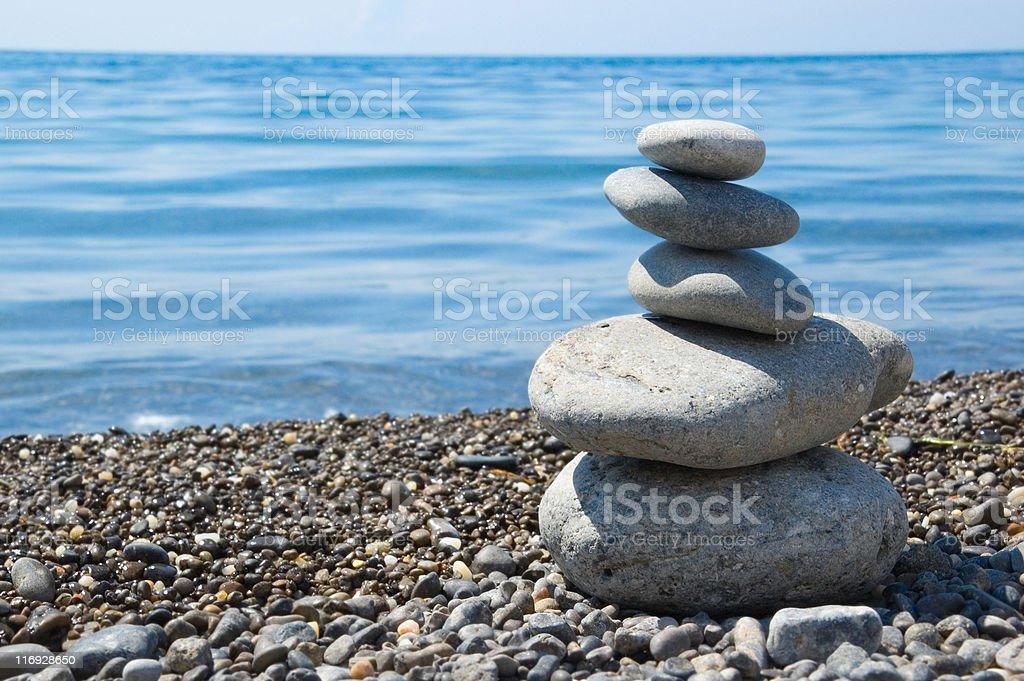 five balanced stones on a beach stock photo