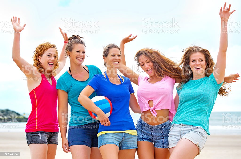 Five beautiful female beach volleyball friends posing for group photo stock photo
