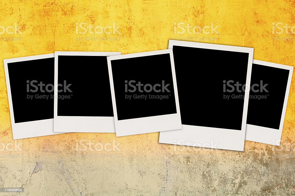 Five Blank Photos on Bright Concrete Wall stock photo