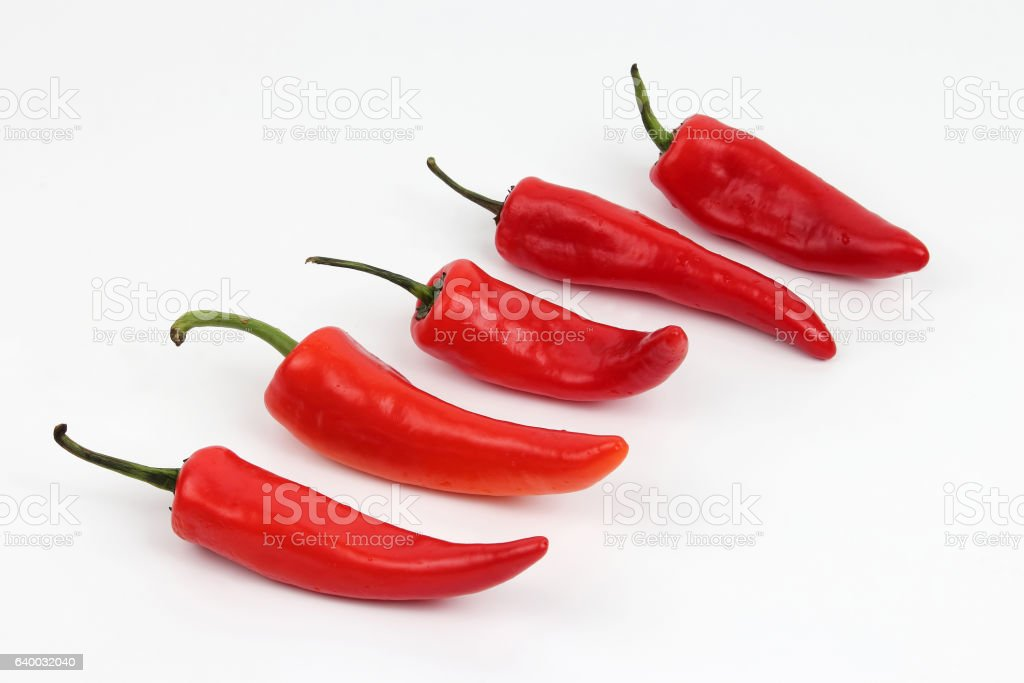 five bright red sweet peppers on a white background stock photo