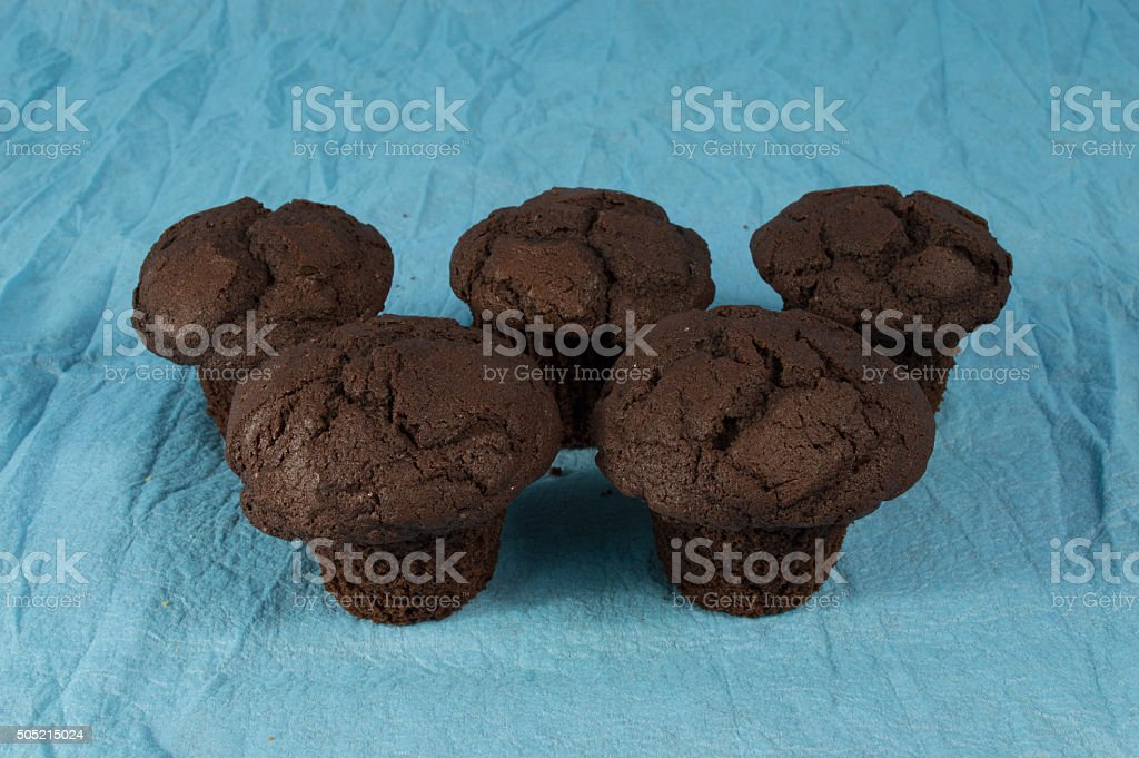 five brown chocolate muffins on a light blue background stock photo