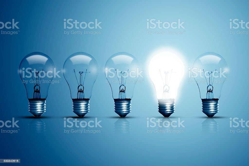 Five bulbs and one of them is glowing. stock photo