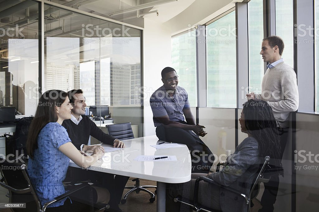 Five business people sitting at a conference table stock photo
