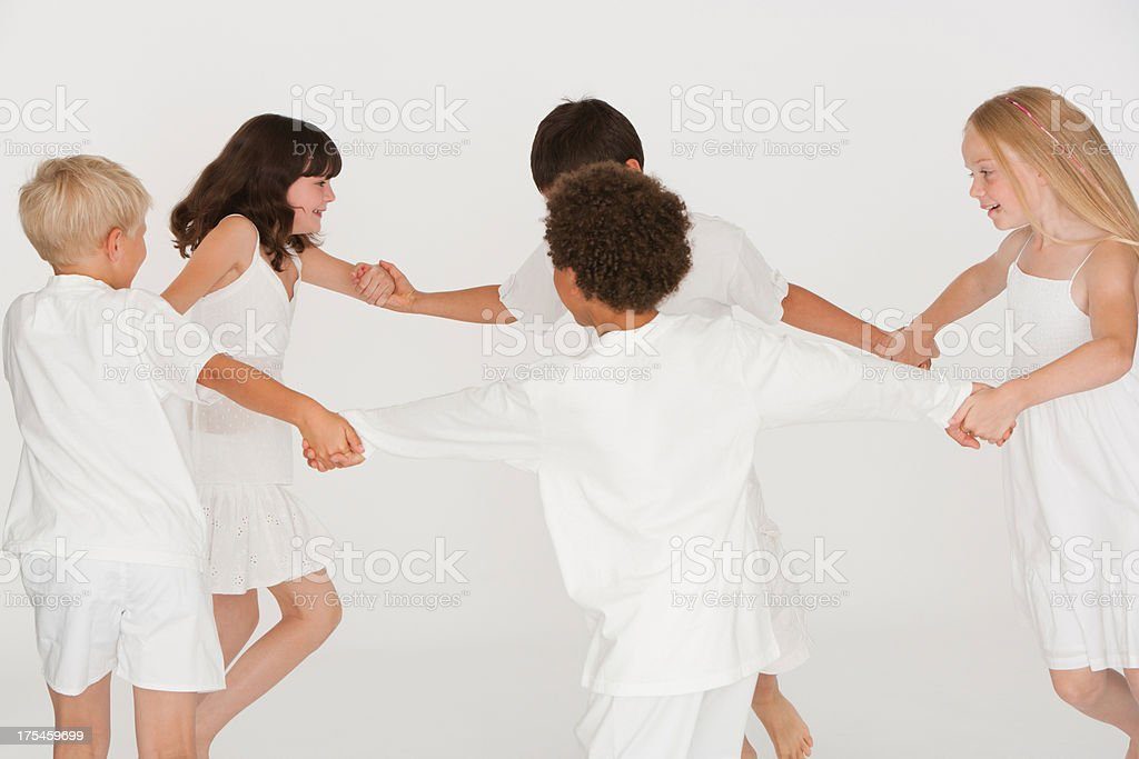 Five children indoors playing ring-around-the-rosie stock photo