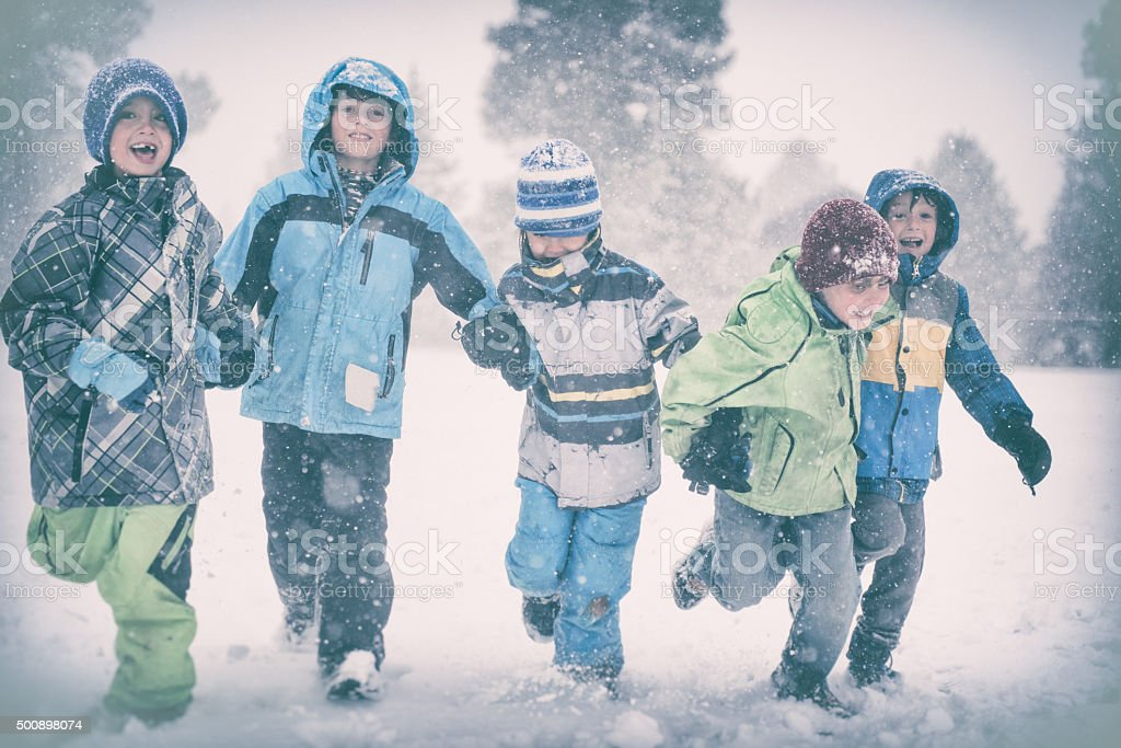 Five children run and play in a snowy storm stock photo