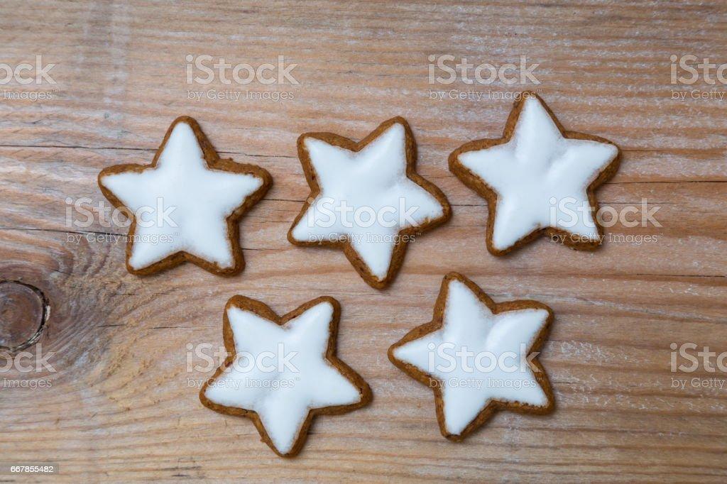 Five cinnamon stars on wood detail stock photo