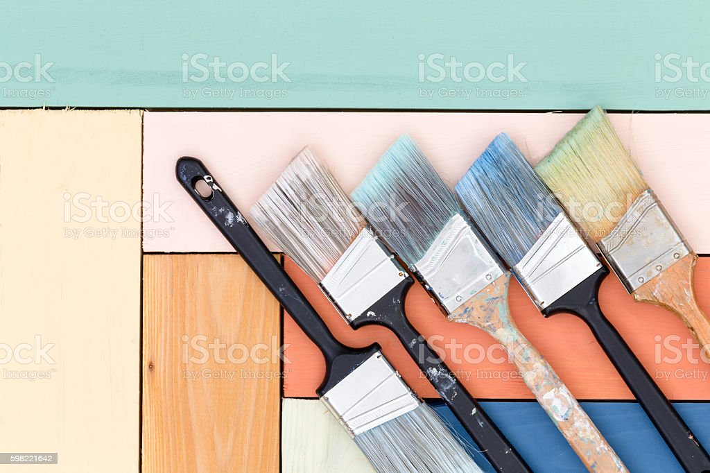 Five cleaned used paintbrushes on stained wood stock photo