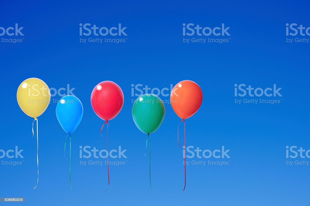 Five colorful balloons floating in a clear sky stock photo