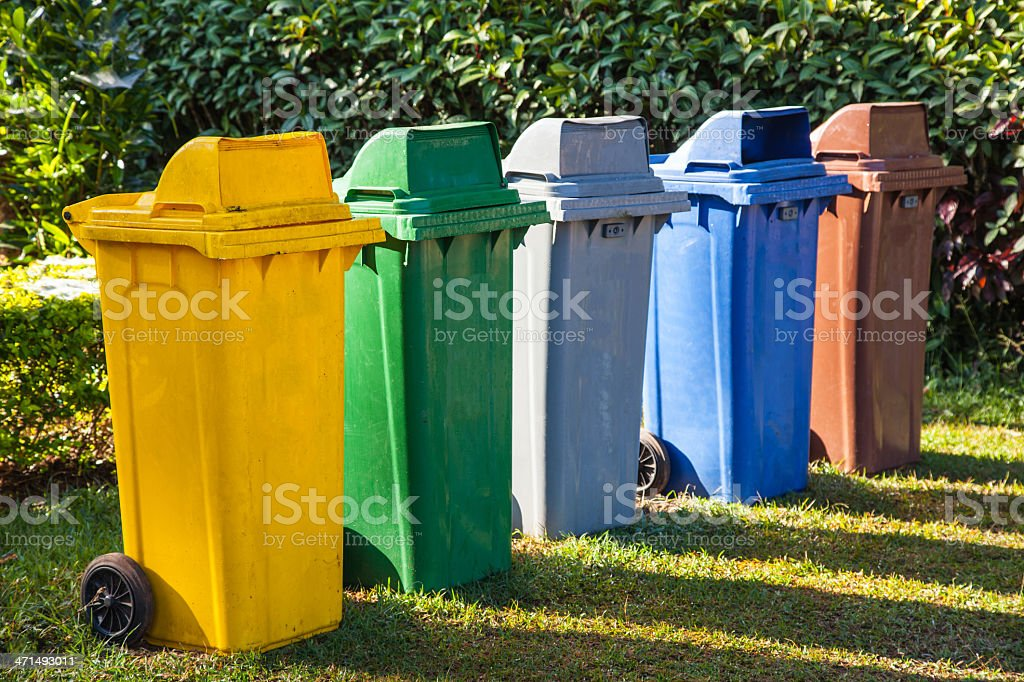 five colors recycle bins in the garden royalty-free stock photo