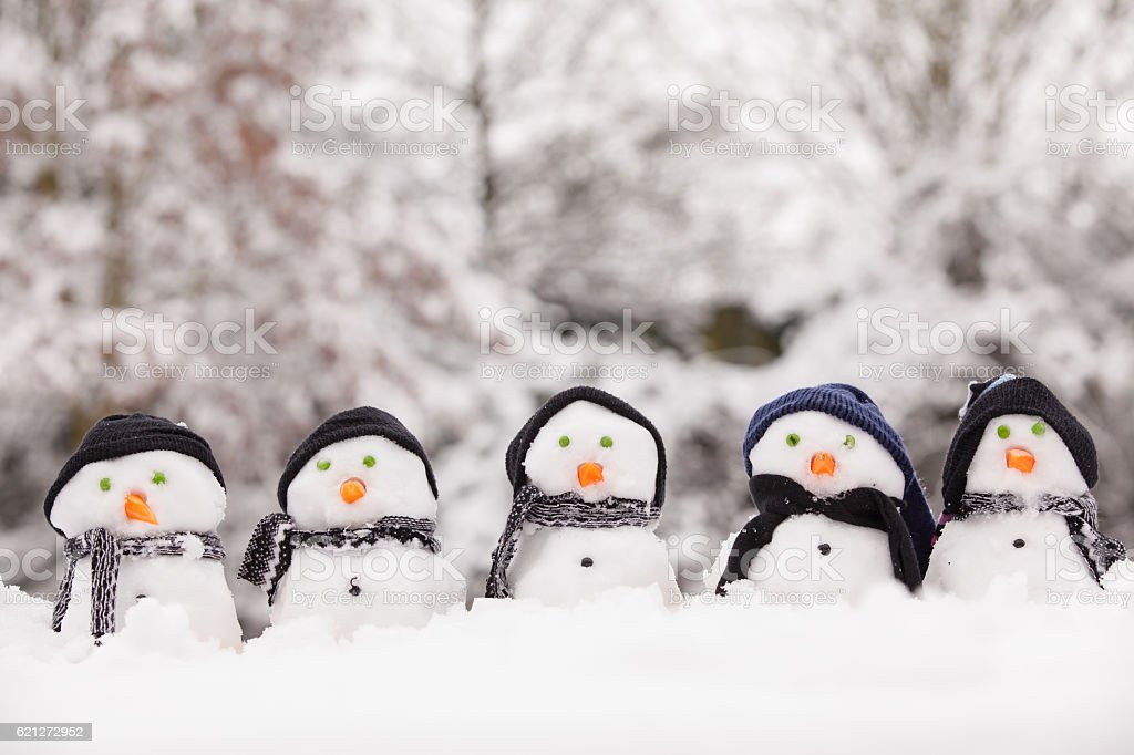 Five cute snowmen facing forward stock photo