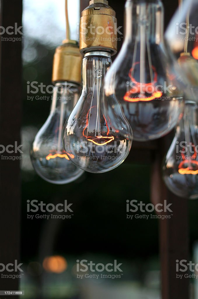 Five dim light bulbs with glowing filaments stock photo