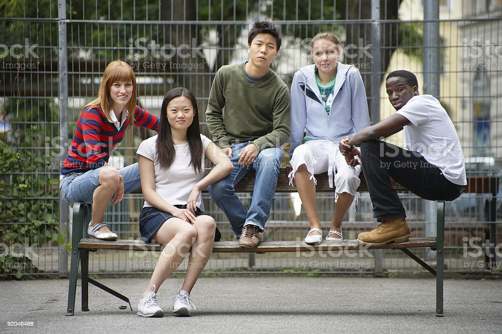 Five diverse young people sitting on a bench royalty-free stock photo