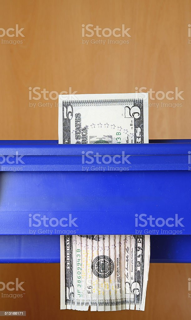 Five dollar bill being destroyed in paper shredder stock photo