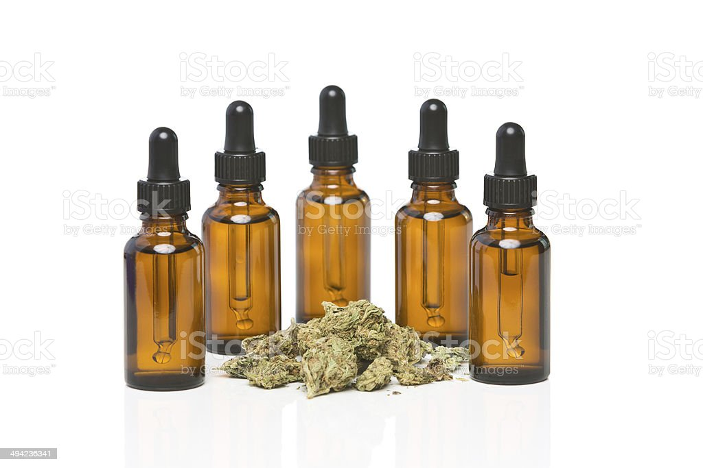 Five dropper bottles surrounding a pile of cannabis royalty-free stock photo