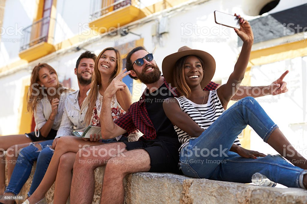 Five friends sitting on a wall in Ibiza taking a selfie stock photo