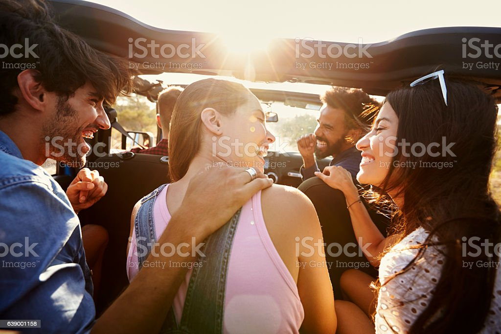 Five friends travelling together on a road trip in a car stock photo