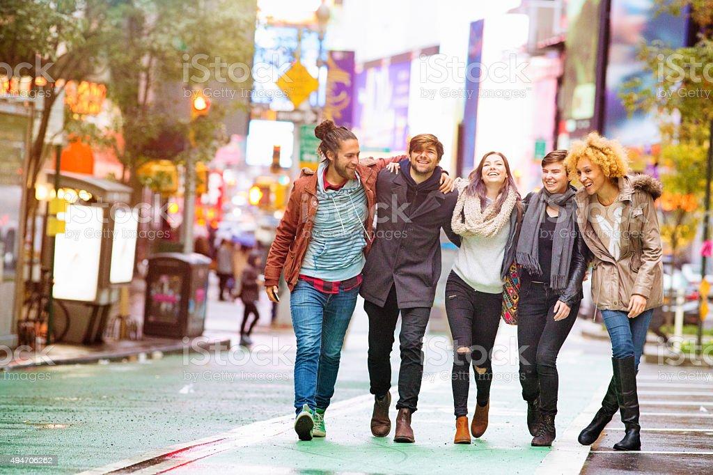 Five friends walking happy in Manhattan wet Autumn day stock photo