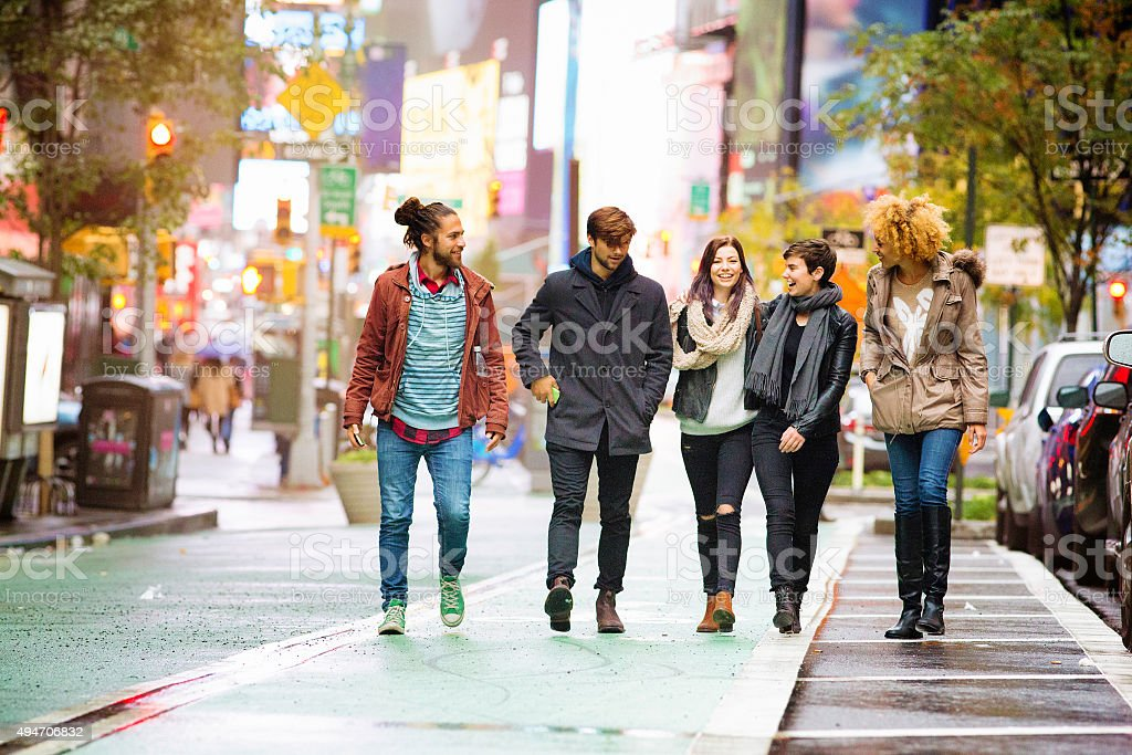 Five friends walking happy in Times square Manhattan stock photo