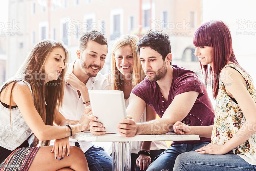 Five friends watching a tablet sitting at a table stock photo