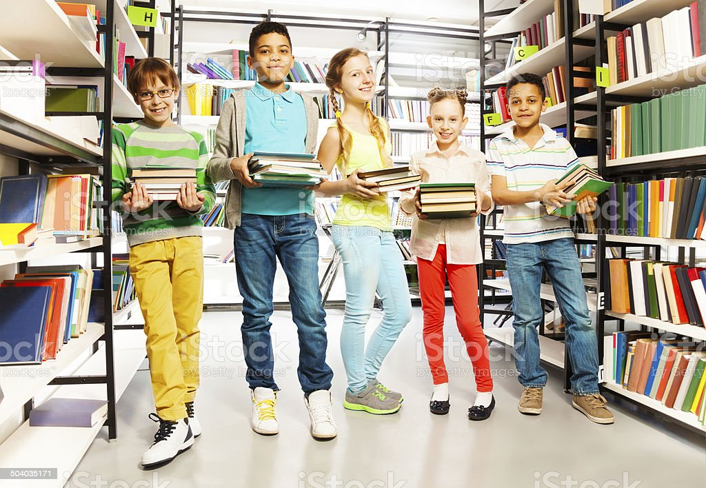 Five friends with piles of books in library stock photo
