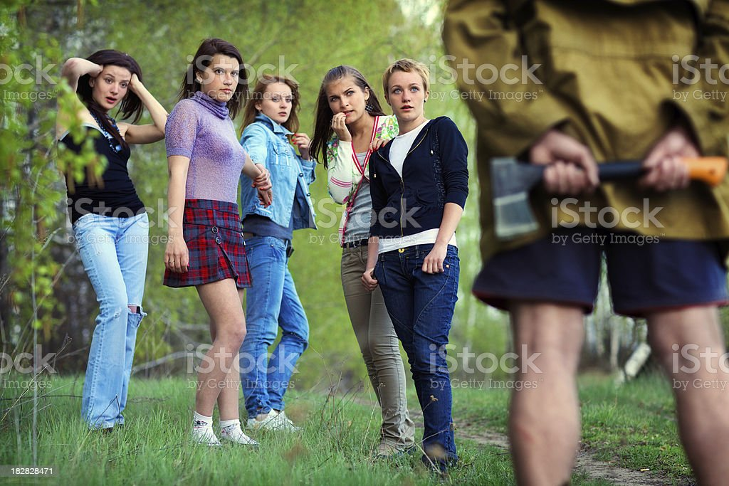 Five girls saw in the woods maniac with an axe royalty-free stock photo