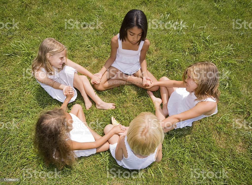 Five girls wearing white sitting in a circle royalty-free stock photo
