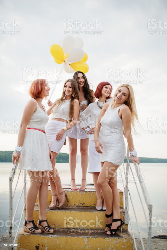 Five girls with balloons at hand weared on white dresses on hen party against pier on lake. stock photo