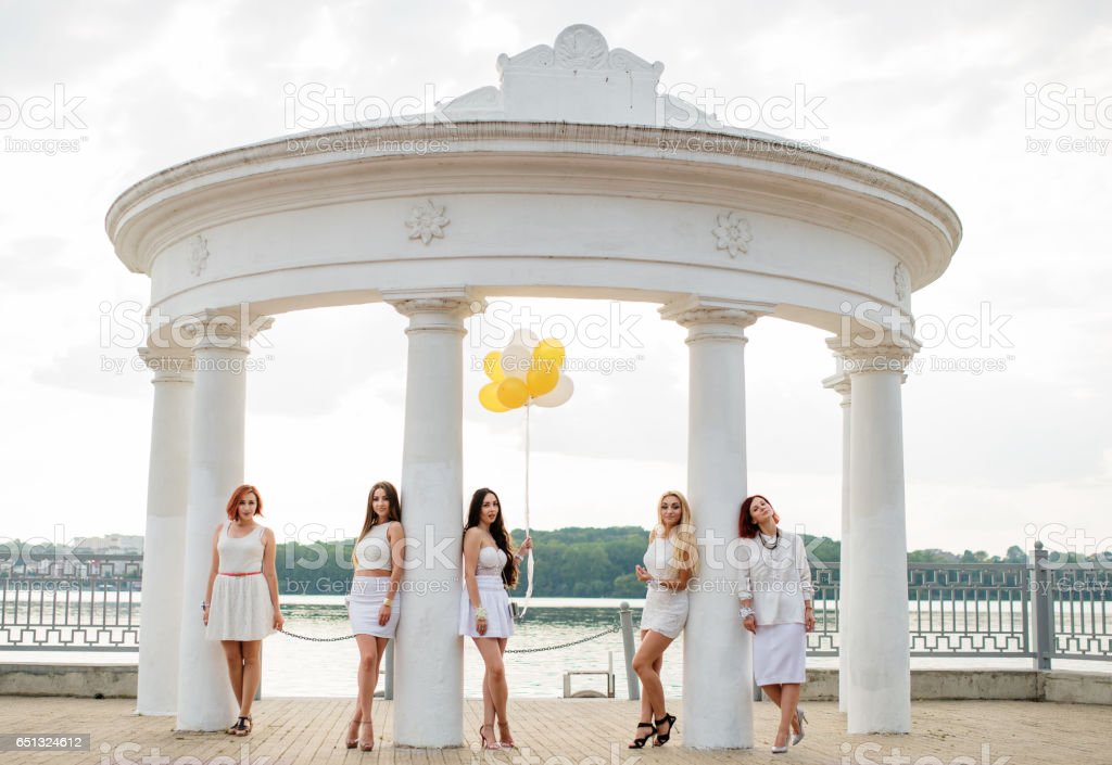 Five girls with balloons at hand weared on white dresses on hen party against white columns of arch. stock photo