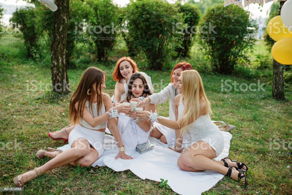 Five girls with champagne at hand weared on white dress on hen party sitting outdoor at park and having fun. stock photo