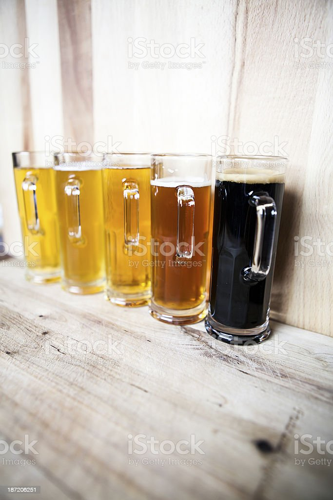 Five glasses of beer on wooden shelf ordered light to dark royalty-free stock photo