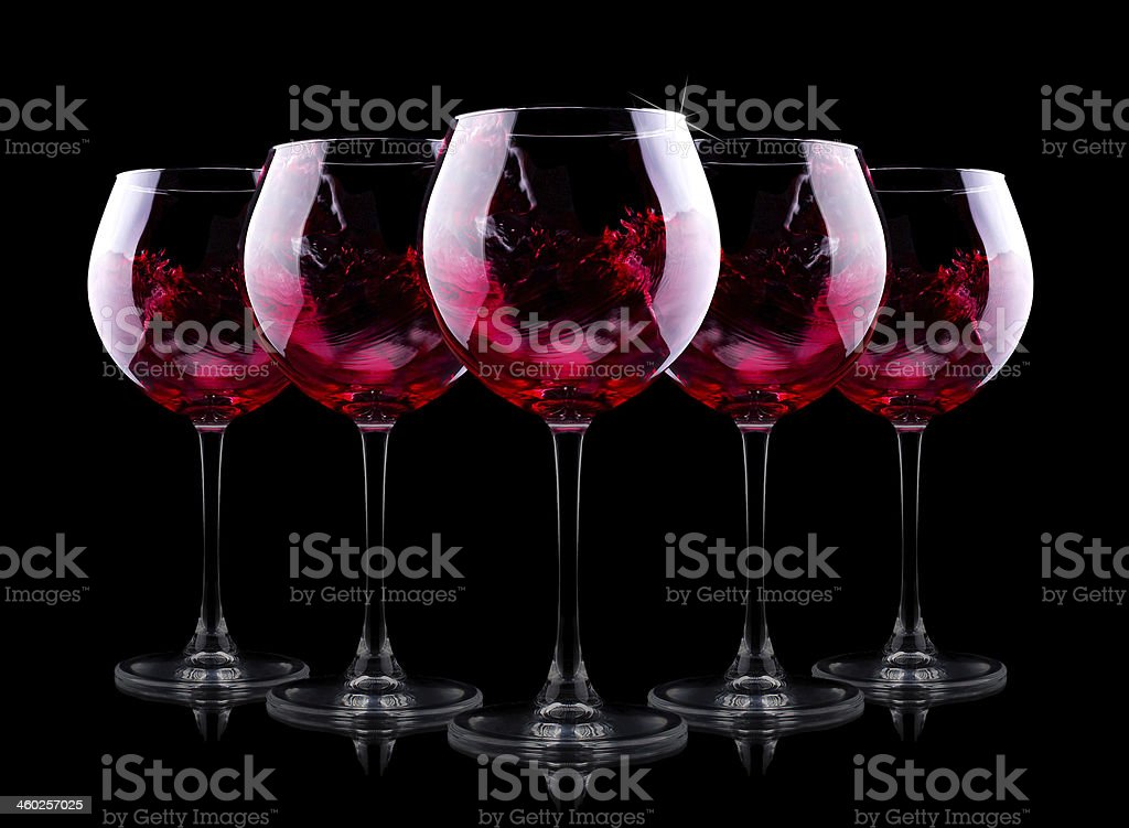 Five glasses of red wine on a black background stock photo