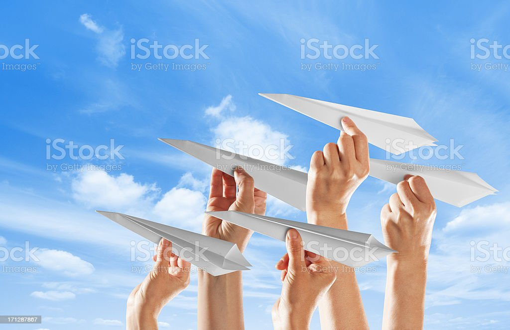 The hands of five family members holding white paper origami...