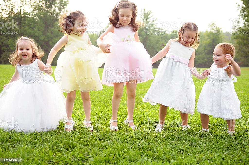 Five Happy Little Girls in Dresses Jumping Outside royalty-free stock photo