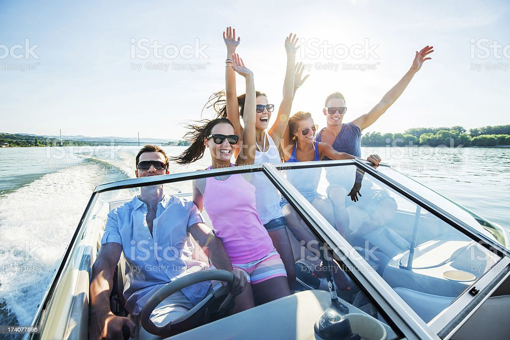 Five happy young people on a speedboat ride stock photo