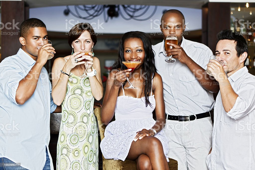 Five happy young people socializing over drinks stock photo